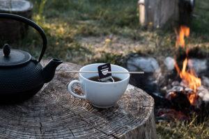 Kop med emeyu te, på træstrup foran bål.